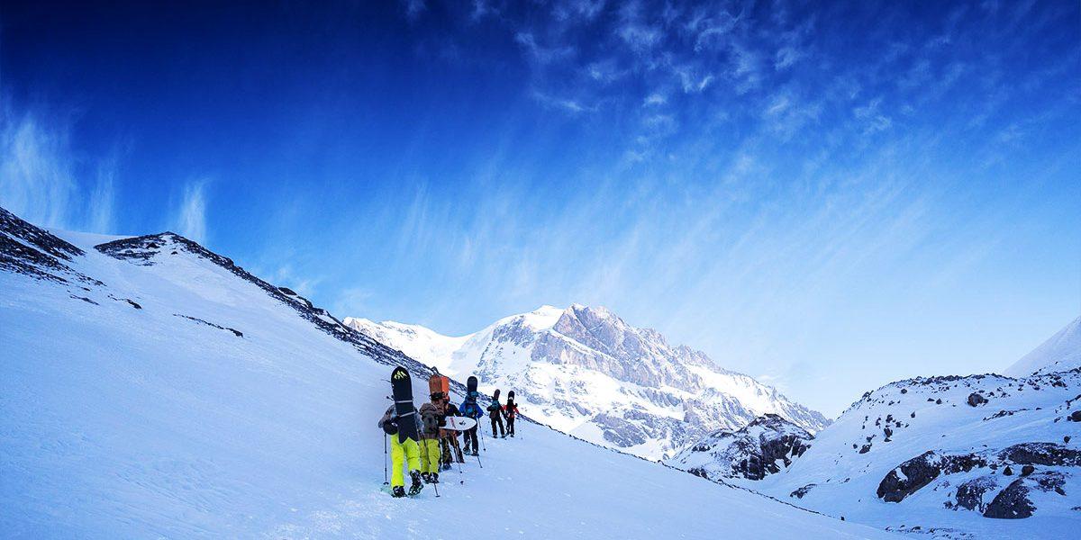 Snowboard Camp members treking up a a mountain