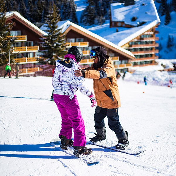 Snowboard tutor giving an individual a lesson